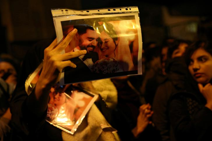 FILE PHOTO: A woman holds a picture of newlyweds, victims of the crash of the Boeing 737-800 plane, flight PS 752, as people gather to show their sympathy in Tehran, Iran January 11, 2020. Nazanin Tabatabaee/WANA (West Asia News Agency) via REUTERS ATTENTION EDITORS - THIS IMAGE HAS BEEN SUPPLIED BY A THIRD PARTY/File Photo