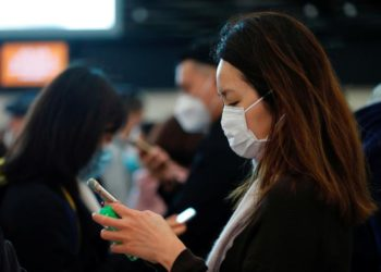 Passengers wear masks to prevent an outbreak of a new coronavirus at the Hong Kong West Kowloon High Speed Train Station, in Hong Kong, China January 23, 2020. REUTERS/Tyrone Siu