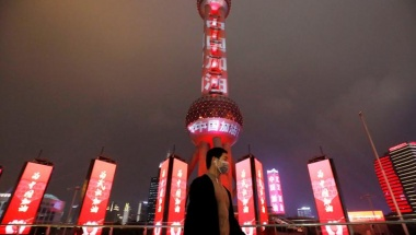 "A man wearing a face mask walks past the Oriental Pearl Tower lit with messages reading ""Stay strong China"", on the Lantern Festival, which marks the end of the Chinese Lunar New Year celebrations, following an outbreak of the novel coronavirus in the country, in Shanghai, China February 8, 2020. Picture taken February 8, 2020. cnsphoto via REUTERS   ATTENTION EDITORS - THIS IMAGE WAS PROVIDED BY A THIRD PARTY. CHINA OUT."