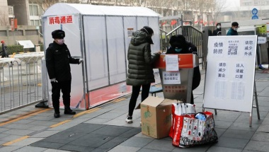 "A security guard stands outside a plastic tent set up to disinfect people coming in at the entrance of a residential compound, as the country is hit by an outbreak of the new coronavirus, in Beijing, China February 13, 2020. The placard at the entrance of the tent reads, ""Disinfection tunnel"". REUTERS/Carlos Garcia Rawlins"