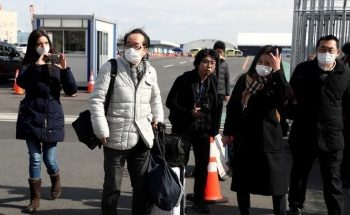 Passengers wearing face masks walk out from the cruise ship Diamond Princess at Daikoku Pier Cruise Terminal in Yokohama, south of Tokyo, Japan February 19, 2020. REUTERS/Athit Perawongmetha