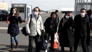 Passengers wearing face masks walk out from the cruise ship Diamond Princess at Daikoku Pier Cruise Terminal in Yokohama, south of Tokyo, Japan February 19, 2020. REUTERS/Athit Perawongmetha