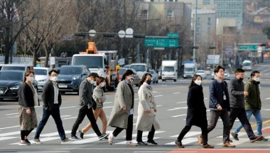 People wearing masks to prevent the coronavirus walk on a pedestrian crossing in downtown Seoul, South Korea, February 24, 2020.    REUTERS/Heo Ran