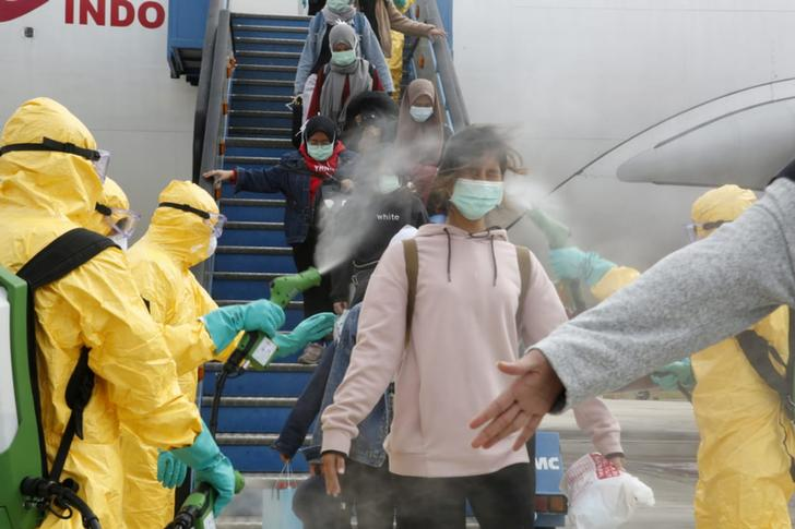 Medical officers spray Indonesian nationals with antiseptic after they arrived from Wuhan, China center of the coronavirus epidemic, before transferring them to the Natuna Islands military base to be quarantined, at Hang Nadim Airport in Batam, Riau Islands, Indonesia, February 2, 2020 in this photo taken by Antara Foto.  Antara Foto/via REUTERS  ATTENTION EDITORS - THIS IMAGE WAS PROVIDED BY A THIRD PARTY. MANDATORY CREDIT. INDONESIA OUT.     TPX IMAGES OF THE DAY