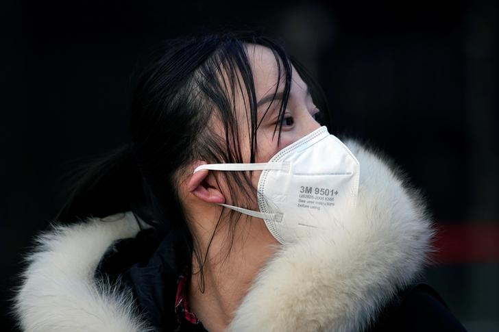 A woman wearing a mask is seen upon her arrival at Shanghai railway station in Shanghai, China, as the country is hit by an outbreak of a new coronavirus, February 2, 2020. REUTERS/Aly Song