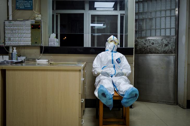 A medical worker in protective suit takes a break during her night shift at a community health service center, which has an isolated section to receive patients with mild symptoms caused by the novel coronavirus and suspected patients of the virus, in Qingshan district of Wuhan, Hubei province, China February 9, 2020. Picture taken February 9, 2020. China Daily via REUTERS  ATTENTION EDITORS - THIS IMAGE WAS PROVIDED BY A THIRD PARTY. CHINA OUT.     TPX IMAGES OF THE DAY