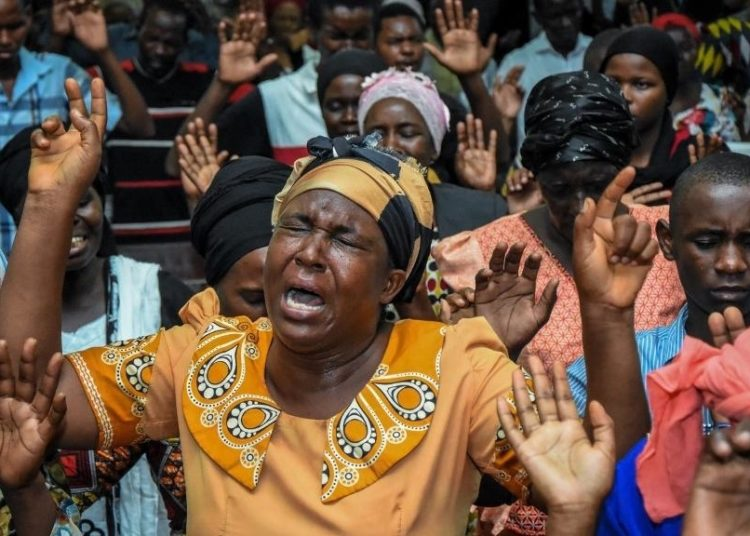 Believers immerse in prayer during a special mass held to usher in the New Year at Full Gospel Bible Fellowship church in Dar es Salaam, Tanzania, on January 1, 2020. (Photo by Ericky BONIPHACE / AFP)