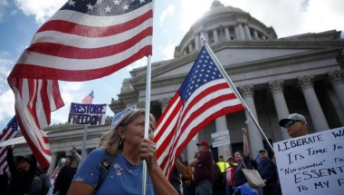 People hold signs and American flags as hundreds protest against the state's extended stay-at-home order to help slow the spread of the coronavirus disease (COVID-19) at the Capitol building in Olympia, Washington, U.S. April 19, 2020. REUTERS/Lindsey Wasson