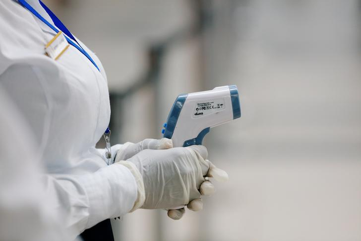 A health worker holds a thermometer as she waits to screen travellers for signs of the coronavirus at the Kotoka International Airport in Accra, Ghana January 30, 2020. REUTERS/Francis Kokoroko