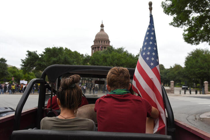 People sit in a car with an American flag as protesters against the state's extended stay-at-home order to help slow the spread of the coronavirus disease (COVID-19) demonstrate at the Capitol building in Austin, Texas, U.S., April 18, 2020. REUTERS/Callaghan O'Hare