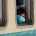 A girl wearing a protective mask looks out from a train window as she returns to her hometown, after Pakistan started easing the lockdown restrictions and allowed to resume passenger trains, following the coronavirus disease (COVID-19) outbreak, in Karachi, Pakistan May 20, 2020. REUTERS/Akhtar Soomro     TPX IMAGES OF THE DAY