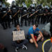 Protesters sit with their backs to riot policemen during nationwide unrest following the death in Minneapolis police custody of George Floyd, in Raleigh, North Carolina, U.S. May 31, 2020. Picture taken May 31, 2020. REUTERS/Jonathan Drake