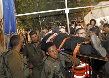 "Medics and members of the Israeli security forces evacuate an injured man after the collapse of grandstand seating at a synagogue in the Israeli settlement of Givat Zeev in the occupied West Bank outside Jerusalem, on May 16, 2021, that left at least 60 people injured. - The incident occurred ""as hundreds were congregated"" for the Jewish Shavuot feast, a spokesman told Israeli channel Kan. (Photo by Gil COHEN-MAGEN / AFP)"