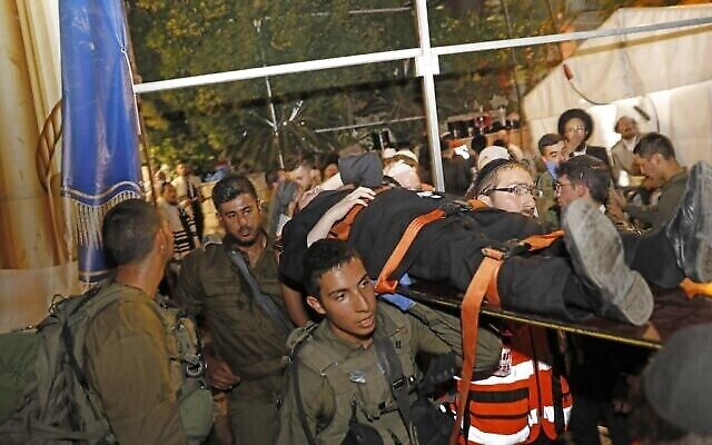 """Medics and members of the Israeli security forces evacuate an injured man after the collapse of grandstand seating at a synagogue in the Israeli settlement of Givat Zeev in the occupied West Bank outside Jerusalem, on May 16, 2021, that left at least 60 people injured. - The incident occurred """"as hundreds were congregated"""" for the Jewish Shavuot feast, a spokesman told Israeli channel Kan. (Photo by Gil COHEN-MAGEN / AFP)"""
